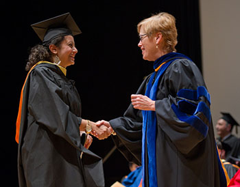 Liddy shakes hands with a student during an iSchool convocation. She forged close relations with many students during her years as a professor and dean.