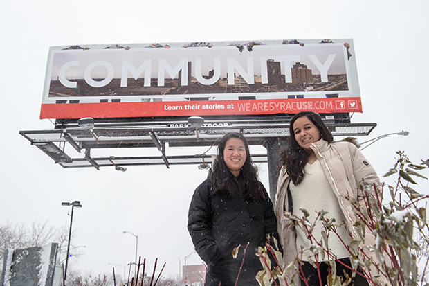 Tiffany Soohoo, left, and Karina Campos stand in front of their billboard in downtown Syracuse.