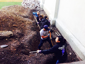 Members of Freedom by Design get down and dirty working on the site of Westminster Presbyterian Church's future ramp.