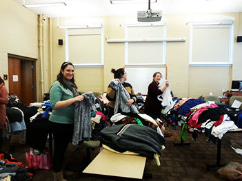Second-year Falk College MFT students organize donations during a January 2015 clothing drive to benefit Syracuse's transgender community. L-R: Jamie Kanter, Melanie Gonzalez, and Megan O'Brien.