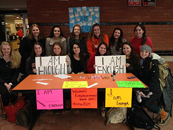 I Am Enough team members and their supporters staff an information table in Schine Student Center.