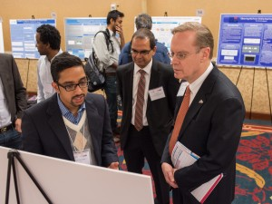 Student Prabesh Rupakheti presents his poster to Chancellor Kent Syverud, right, and Interim Dean Mohan.