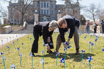 Chancellor Kent Syverud and Dr. Ruth Chen join in the effort to plant pinwheels in the lawn between the Schine Student Center and the Newhouse complex.
