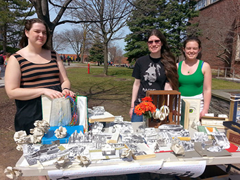 Alexandra Heidler, Emma Esperon, and Margaret Craft with a portion of the  'Upcycled Library' book repurposing display.