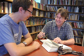 Philosophy Department Chair Ben Bradley, right, meets with a student.