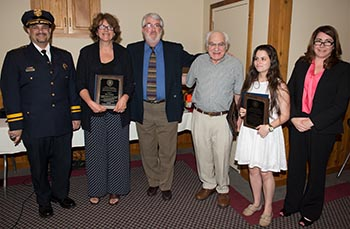 Callisto, left, and Lentz, right, present awards to three community members who assisted in rescuing a fellow student from drowning in Webster Pool. L to R: Mrs. Jeanne O'Leary and Mr. Don O'Leary accept an award in place of their daughter Zoe O'Leary, who's studying abroad; Professor Louis Kriesberg, who alerted the lifeguards that a swimmer had sunk in the pool; and Hanna Mallette.