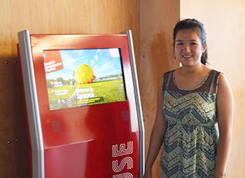Tiffany Soohoo '17, summer intern in the Office of Community and Economic Development, demonstrates the new TAP system to help vistors find asdfsdf in Syracuse.