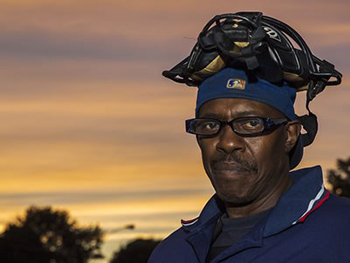 •Dominican umpire Victor Chatman pauses at a game between the West End and Eastwood little leagues at Syracuse's Lewis Park. (Photo by Marilu Lopez Fretts)