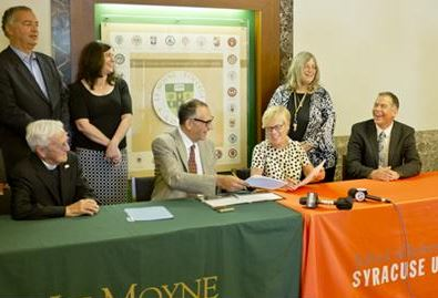 Le Moyne College Interim Provost Thomas Brockelman (left) and Syracuse University Interim Provost Liz Liddy sign the agreement.
