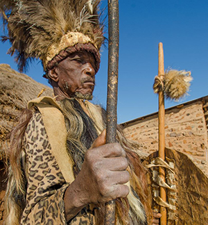 Near the Mozambican border, an elderly tribal chief stands guard over his village in full ceremonial dress.