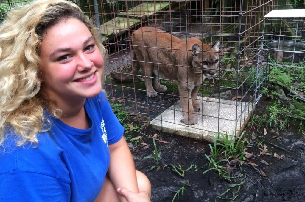 Chiara Vantaggiato next to cougar in cage