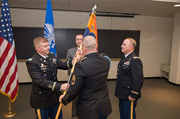 The new leader of the Army ROTC program, Lt. Col. Jason Warner, at right, receives a flag during the Change of Authority ceremony Friday, as J. Michael Haynie, vice chancellor for veterans and military affairs, center, and retiring Lt. Col. Michael Bianchi, at left, look on.