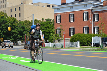 College of Visual and Performing Arts faculty member Zeke Leonard uses the new bike lane along East Genesee Street to commute to work.