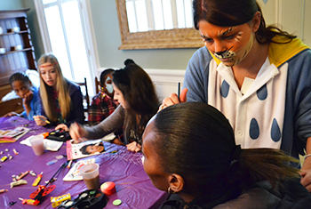 Sosority members paint faces during a previous Greek or Treat event.