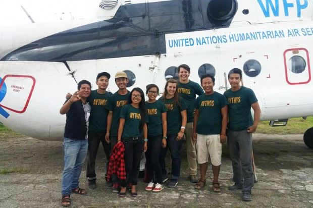 Rachel Penner, fourth from right, and Beau Miller, third from right, stand with other volunteers near a mission transport plane.