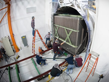 Scientists work on the MicroBooNE detector, which is approximately the size of a school bus (Courtesy of Fermilab)