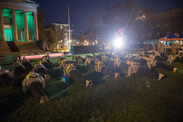 "ROTC members warm up for the Veterans Day Run in front of Hendricks Chapel, which is lit up in green to ""Green Light a Vet,"" and initiative of Walmart."