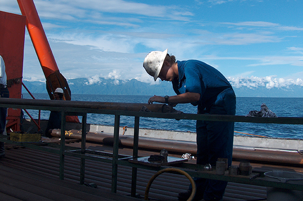 Geological engineer prepares sampling tool for drilling aboard a scientific drilling barge on Lake Malawi. Photo credit: Christopher Scholz