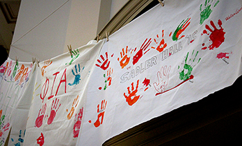 Handcrafted banners symbolize support for survivors and allies.