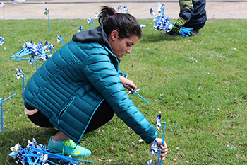 Fallon Hiller, a junior majoring in social work in Falk College, plants pinwheels to denote Child Abuse Prevention Awareness Month in the space between Schine Student Center and the Newhouse Complex.