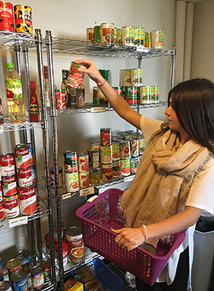 Megan McClellan stocks the shelves at the Hendricks Chapel food pantry.