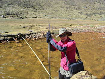 Baker taking data measurements of a mountain stream in Cordillera Blanca, Peru