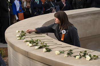 Remembrance Scholar Lisa Kranz lays a rose at the Place of Remembrance during a ceremony in October 2015.