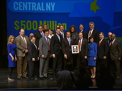 Chancellor Syverud (just right of center) poses with Gov. Cuomo and others in December 2015 after the announcement that Central New York was one of three regions that would receive $500 million in economic development funds.