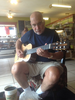 Donald Siegel playing guitar at Picasso's Pastries and Café