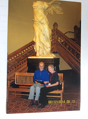 "Joan Kibbe and her husband, Richard Scaramelli, sit in front of ""Winged Victory"" in Crouse College in 2014."