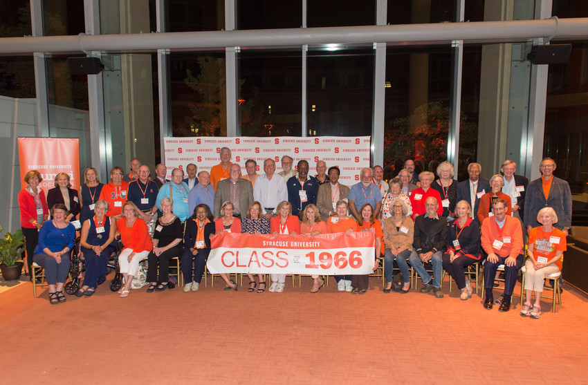 alumni in front of banner