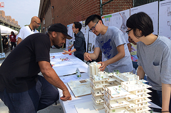 "Yuchi Kuo, center, and Yen Hsi Tung, right, Syracuse Architecture students in the ""NYC: Housing for the Public"" course share ideas with a Brownsville resident at a local street fair."