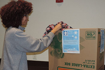 A student drops off a donation for the campuswide winter coat drive.