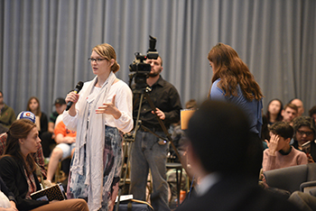 "Syracuse University student Darci Pauser asks for questions from the crowd during a panel called the ""Geopolitical Situation in Syria"" as part of the ""Running for Cover in the Syrian Conflict"" symposium in the Joyce Hergenhan Auditorium at Syracuse University's S.I. Newhouse School of Public Communications. Photo by Tony D. Curtis."