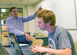 iSchool Professor Jeff Rubin works with one of the MLB Challenge students teams during the 2015 contest.
