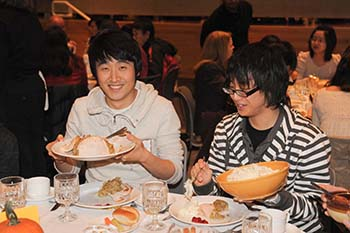 Students enjoy the meal at a previous International Thanksgiving Celebration.