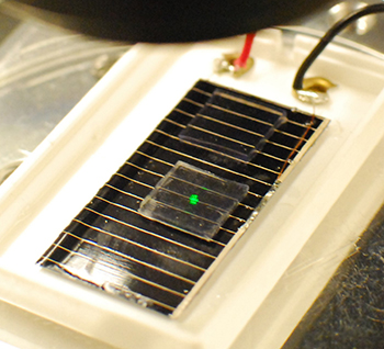 A beam of light is directed toward a solar cell covered with a newly developed plastic coating that enables increased light capture.