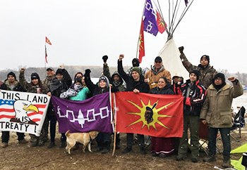 Members of Central New York's Haudenosaunee Confederacy pose at Standing Rock, holding their signature purple flag. (Photo by Kacey Chopito)