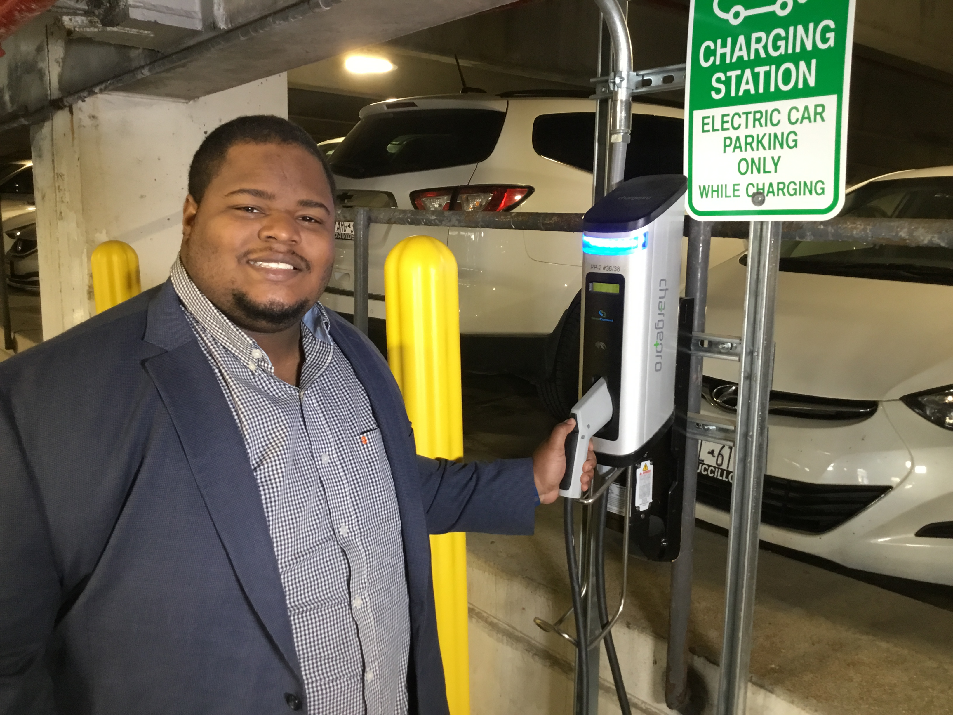 Josh Aviv '14 and a graduate student in the iSchool, stands next to the electric vehicle charger he donated to the University.