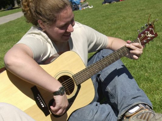student playing guitar on the quad