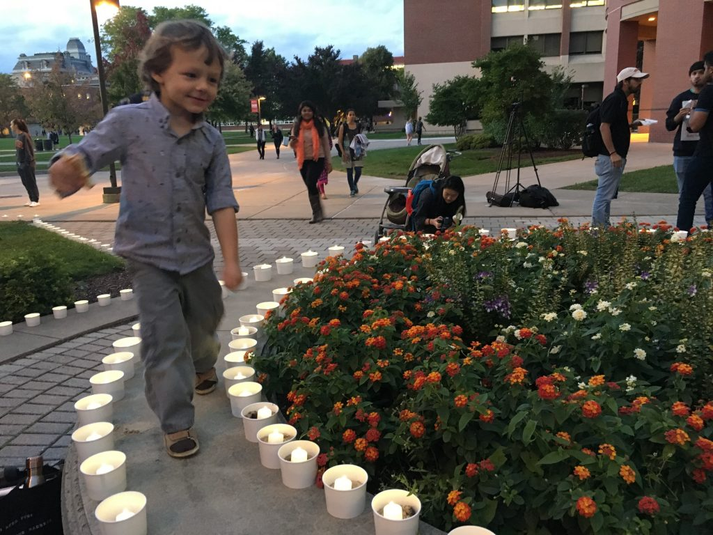 boy walking around candles