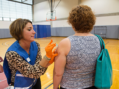 Photo: Employee receiving a flu shot from pharmacist