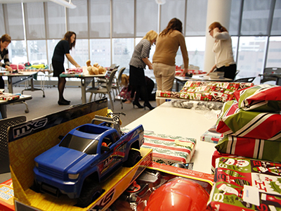 Photo: people wrapping gifts for holiday giving