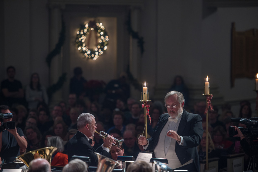 man conducting orchestra in front of audience