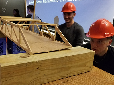 student engineers with their bridge