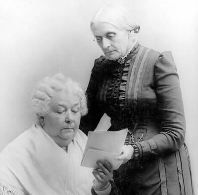 one woman sitting, one woman standing looking at letters