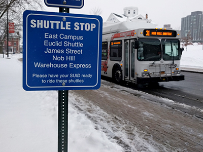 Shuttle stop sign with bus in the background