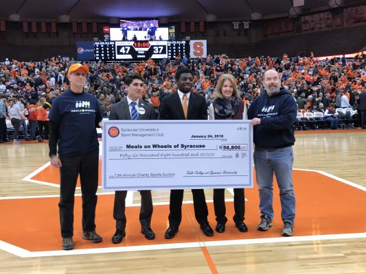 Members of the sport management club present large check to representatives from Meals on Wheels. Check reads 56,800 dollars.