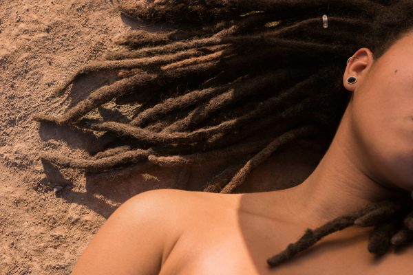 photo of woman's shoulder, part of her face and dreadlocks lying on sand