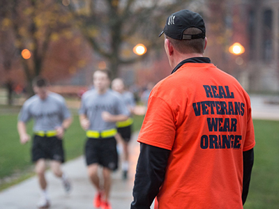 "Man with ""Real Veterans Wear Orange "" T-shirt watching runners"